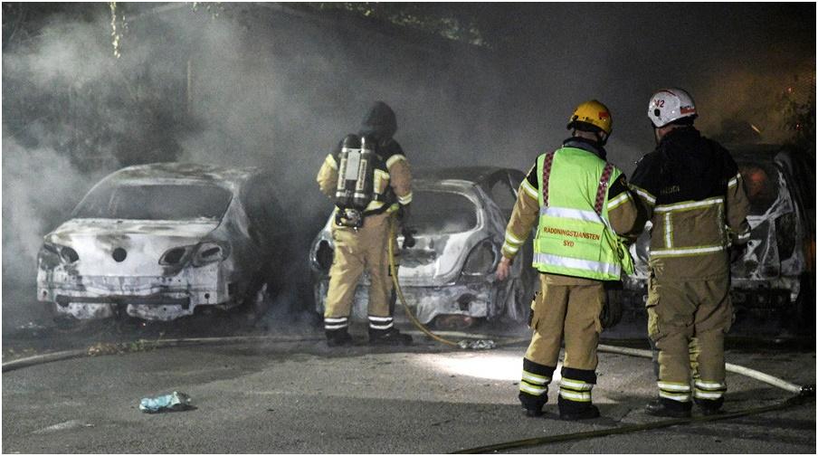 Tűzoltó felgyújtott kocsikat oltsanak Malmö-ben (Svédország)